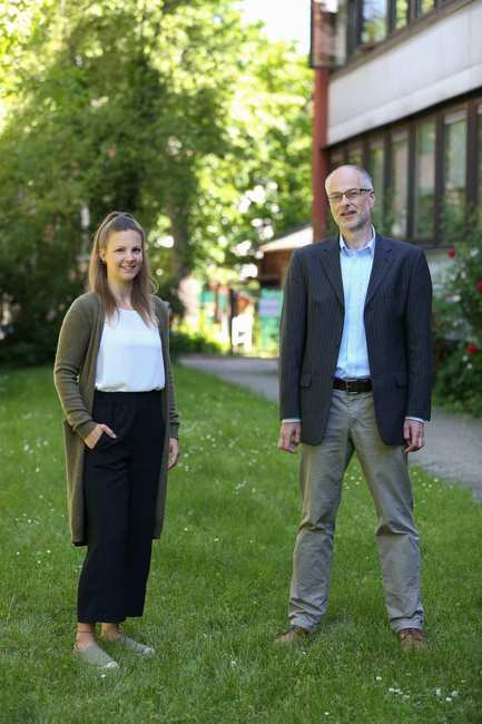 Eine Frau und ein Mann stehen auf einer Wiese vor einem großen Haus und schauen in die Kamera.