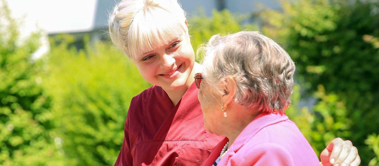 Eine Pflegekraft unterhält sich mit einer älteren Frau in einem Garten.