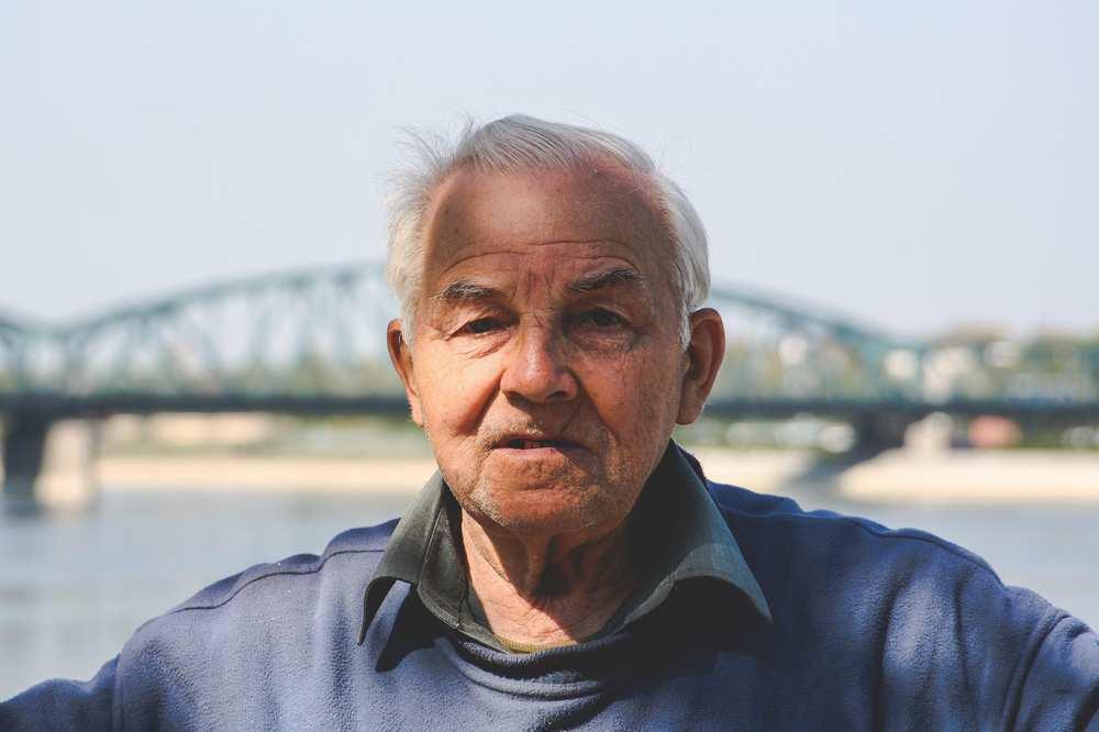 Ein älterer Mann. Im Hintergrund ist eine Brücke über einen Fluss zu sehen.