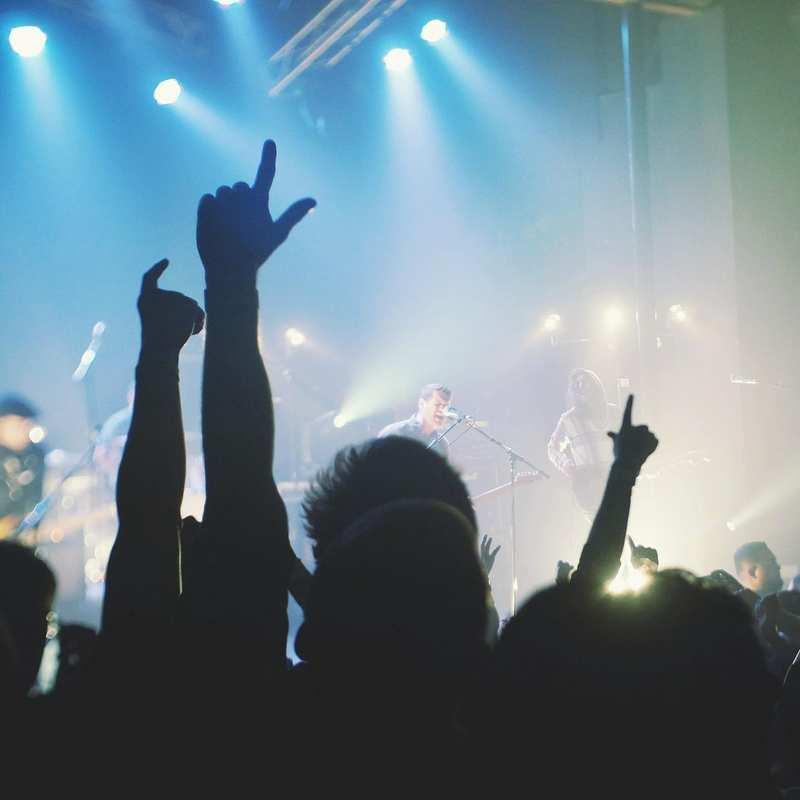 Ein Konzert einer Musikgruppe. Im Vordergrund sieht man die erhobenen Hände der Gäste. Im Hintergrund sieht man den Sänger und Gitarristen der Band.