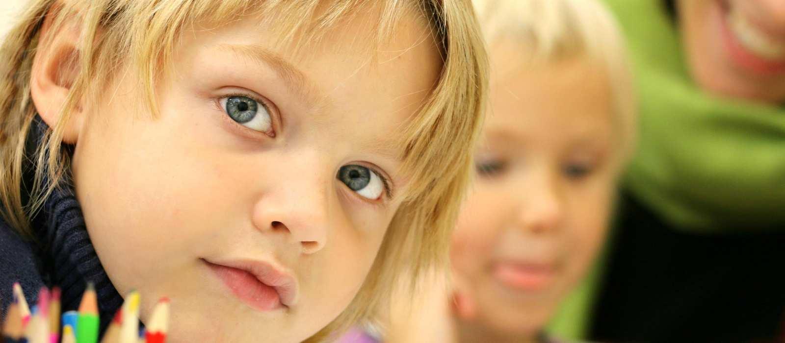 Ein Kind schaut in die Kamera. Am Tisch ist noch ein Kind und eine erwachsene Frau, die sich über das Kind beugt.