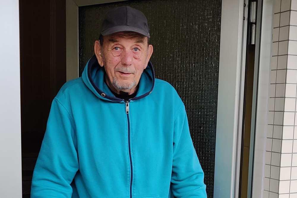 Ein Mann, der einen Umzugskarton trägt, tritt aus einer Tür.