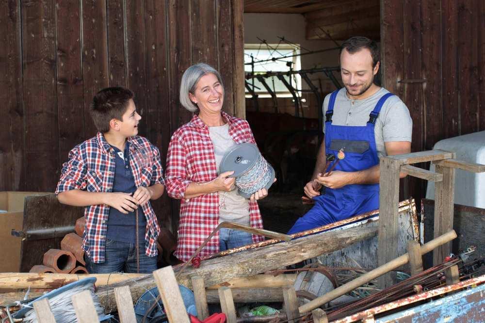 Ein Junge, eine ältere Frau und ein junger Mann stehen vor einem Kuhstall. Die Frau trägt eine Rolle, auf der ein elektrischer Weidezaun für Rinder aufgewickelt ist. Der Mann hat zwei Stangen mit Isolatoren in Händen.