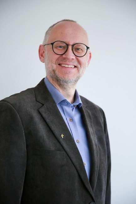 Portrait eines älteren Mannes mit Brille, graumeliertem Haar und Drei-Tage-Bart.