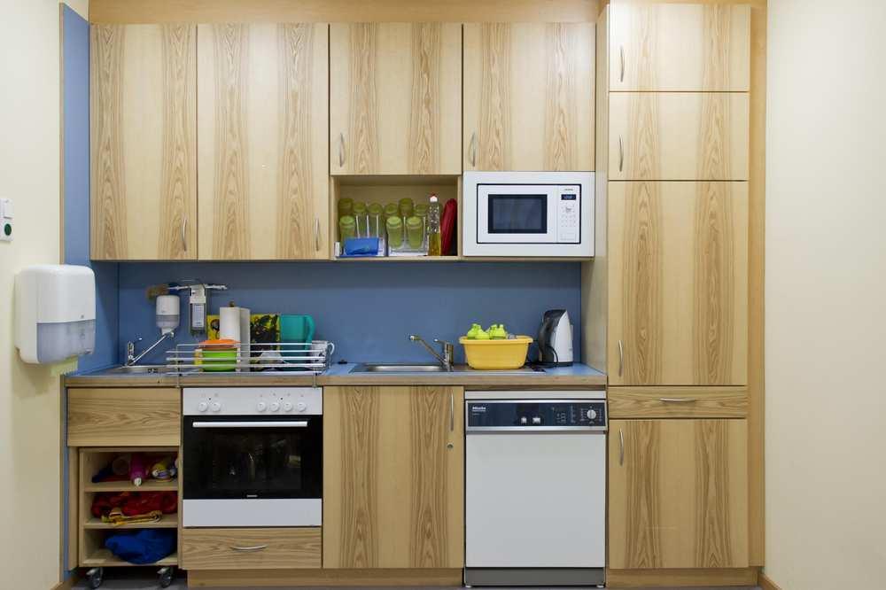 Eine Küchenzeile mit Spüle, Backofen, Spülmaschine, Kühlschrank sowie Hängeschränken aus hellem Holz.