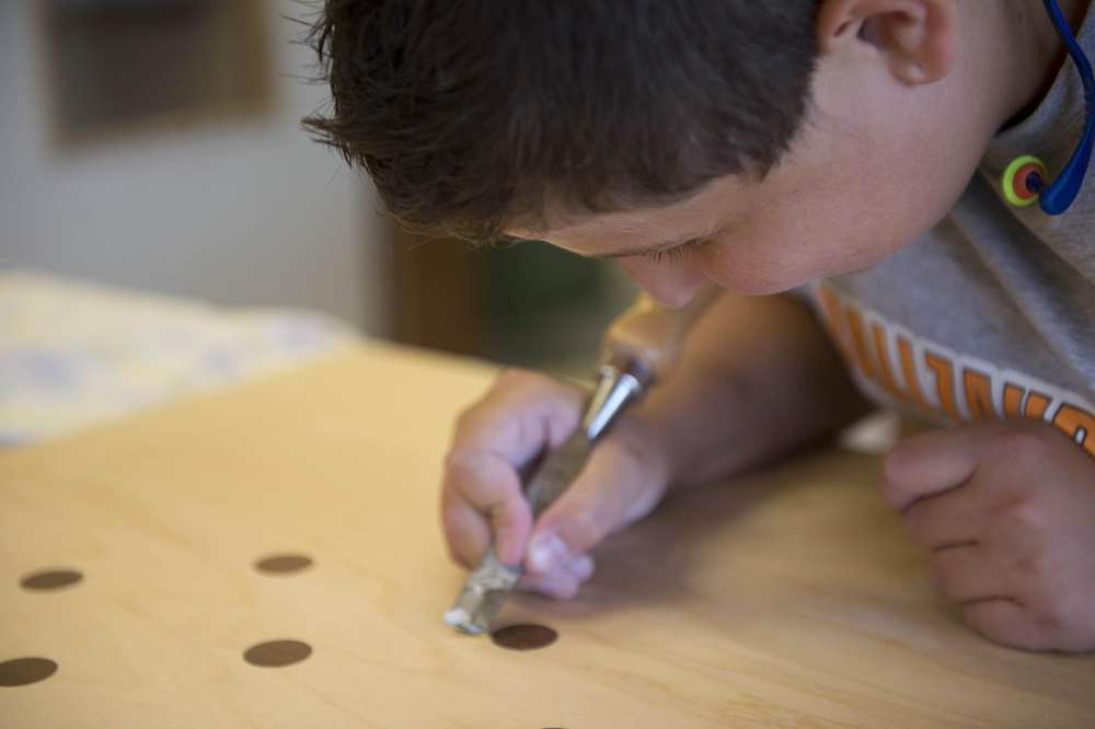 Ein junger Mann beugt sich über ein Werkstück und entgradet gebohrte Löcher.