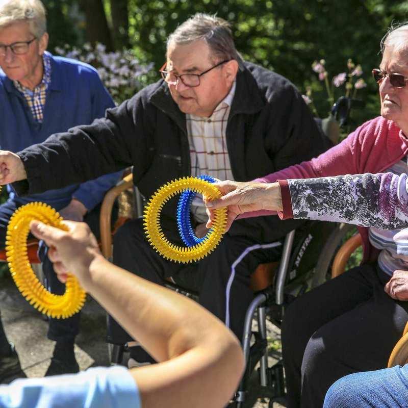 Mehrere Personen sitzen in einem Stuhlkreis und halten farbige Gymnastikringe in die Mitte des Kreises.
