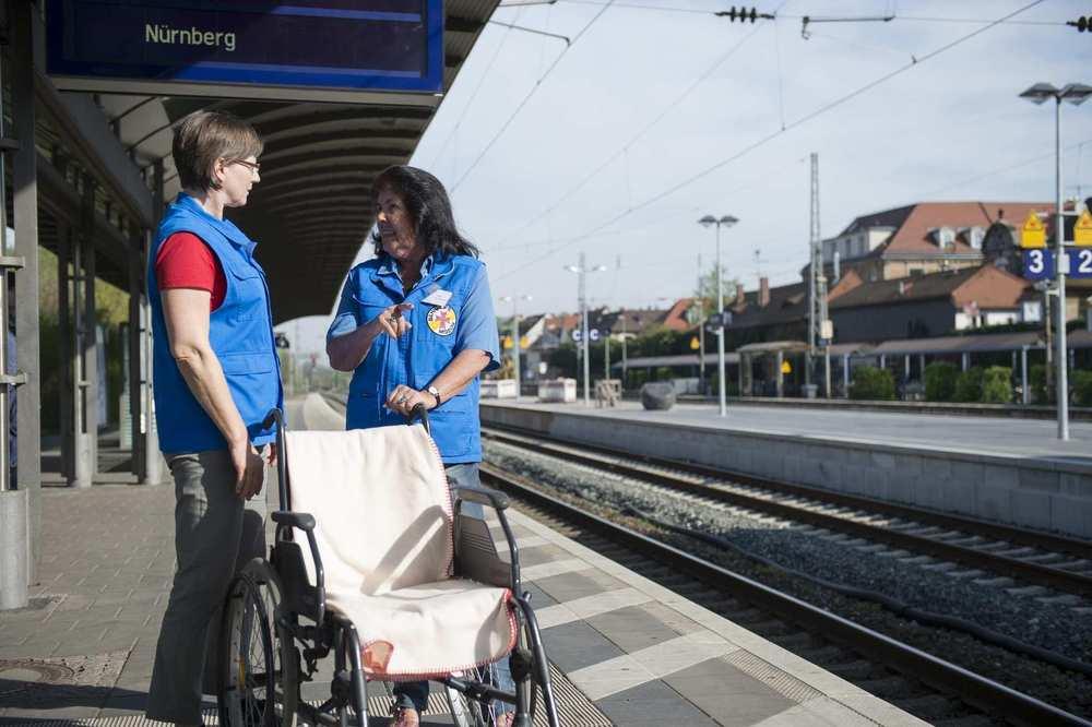 Zwei Mitarbeiterinnen der Bahnhofsmission stehen mit einem Rollstuhl am Bahngleis.