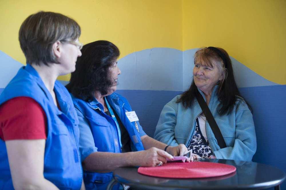 Zwei Mitarbeiterinnen der Bahnhofsmission befinden sich mit einer weiteren Frau an einem runden Stehtisch und unterhalten sich.