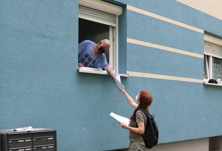 Eine Frau mit Rucksack reicht einem Mann von der Straße aus Unterlagen durchs Fenster. Beide tragen einen Mundschutz.