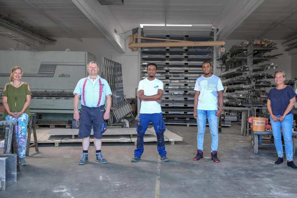 Zwei Frauen und drei Männer stehen in einer Werkhalle.