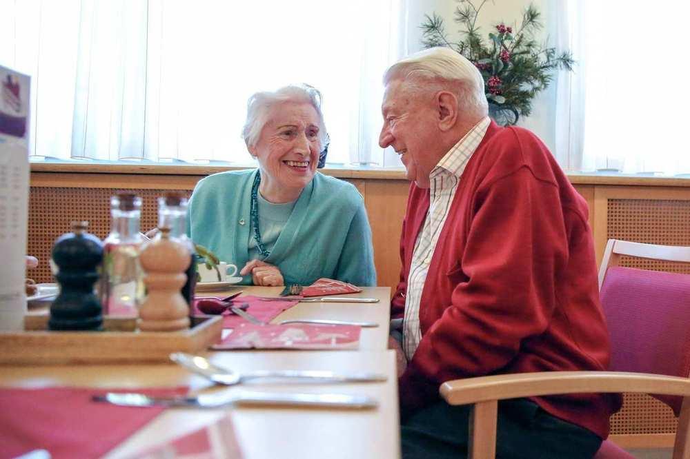 Zwei ältere Personen sitzen an einem Tisch und unterhalten sich.