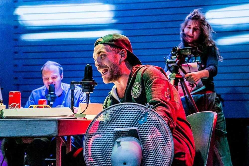 Zwei Männer und eine Frau sind auf einer Theaterbühne. Die Männer haben Mikrophone neben sich, die Frau hält eine Kamera.