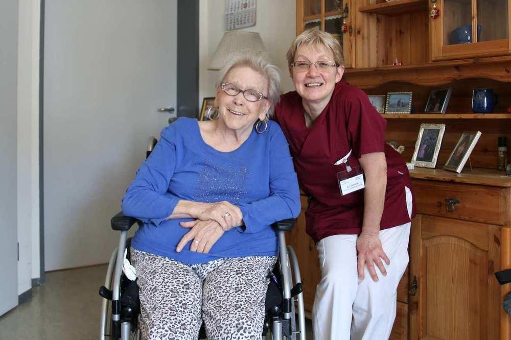 Eine Bewohnerin sitzt im Rollstuhl, eine Pflegekraft steht neben ihr. Im Hintergrund ist eine Holzkommode.