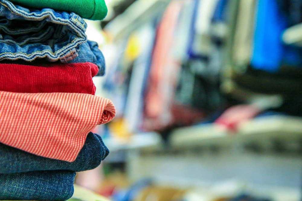 Im Vordergrund befindet sich ein zusammengelegter Kleidungsstapel. Im Hintergrund sind Kleider an einer Stange aufgereiht.