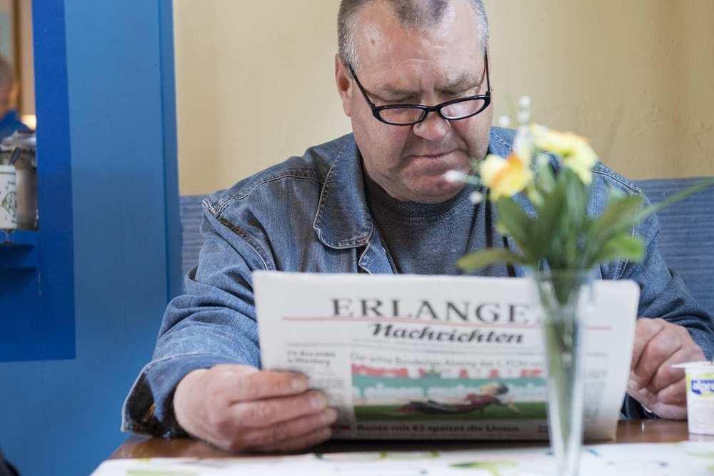 Ein Mann mit Brille sitzt zeitungslesend an einem Tisch.