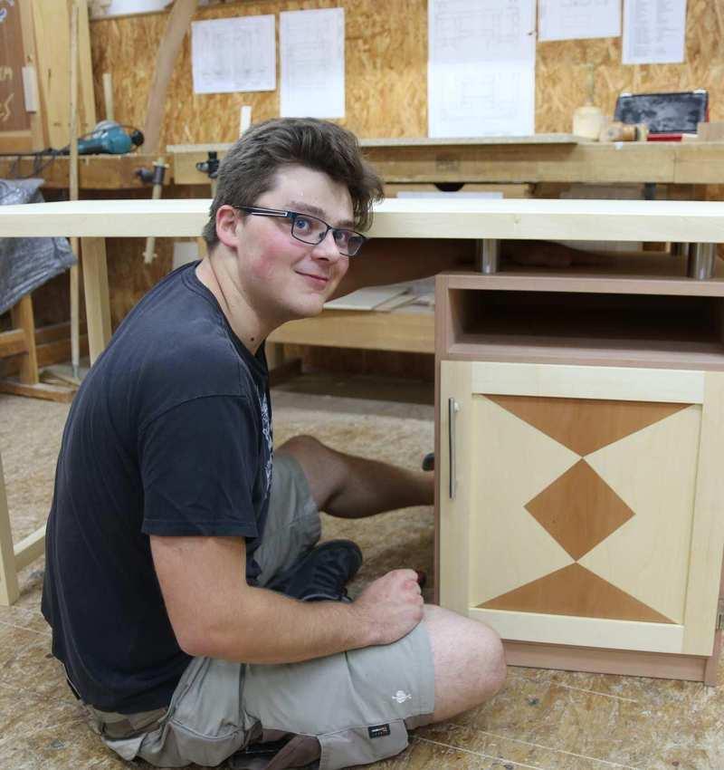 Ein junger Mann sitzt neben einem Schreibtisch, den er selbst hergestellt hat.