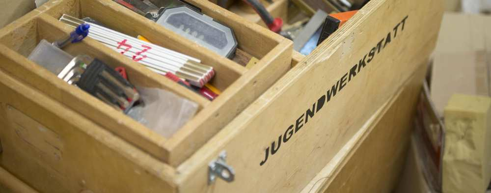 Ein Werkzeugkasten der Jugendwerkstatt. Die verschiedenen Fächer sind mit unterschiedlichen Werkzeugen gefüllt.