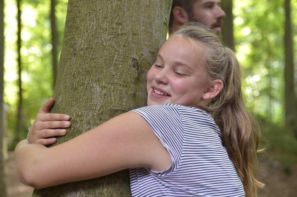 Ein Kind umarmt einen Baumstamm.