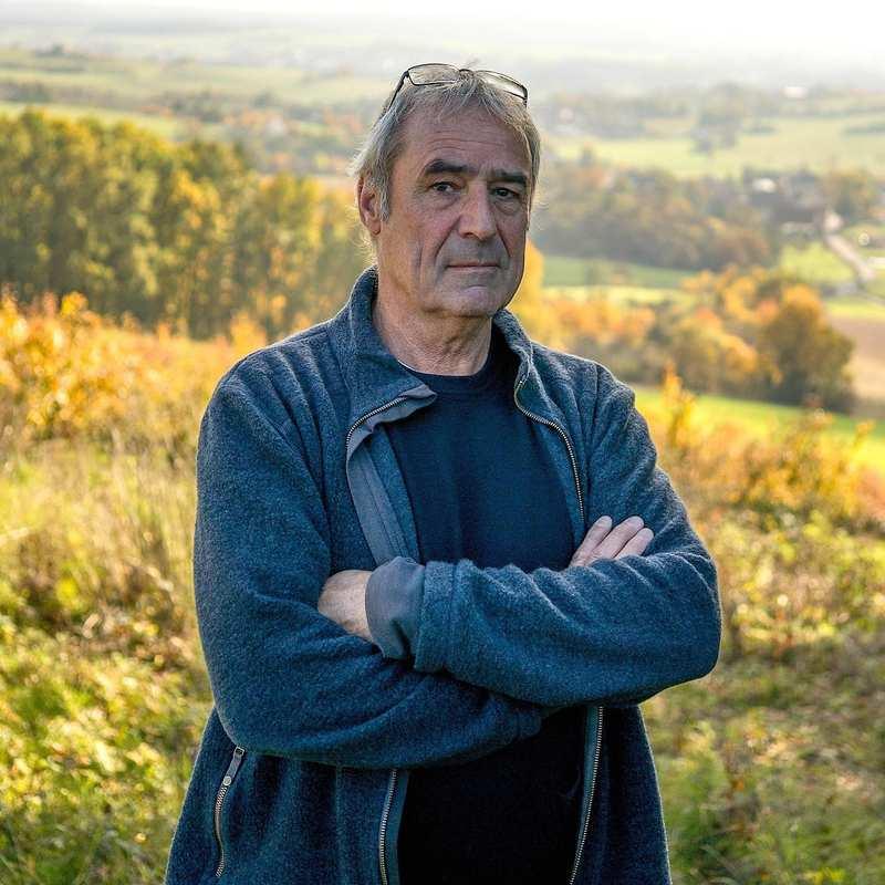 Ein älterer Mann steht mit verschränkten Armen auf einer Anhöhe. Im Hintergrund sind Wiesen, Felder und Bäume.