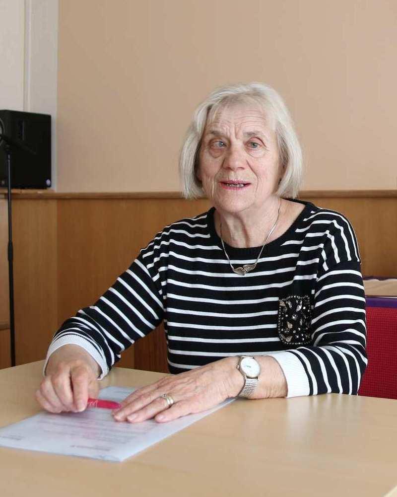 Eine Frau sitzt an einem Tisch und hat ein Blatt Papier vor sich.
