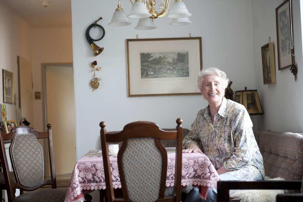 Eine ältere Frau sitzt an einem Tisch. An der Wand hinter ihr hängen mehrere Bilder.