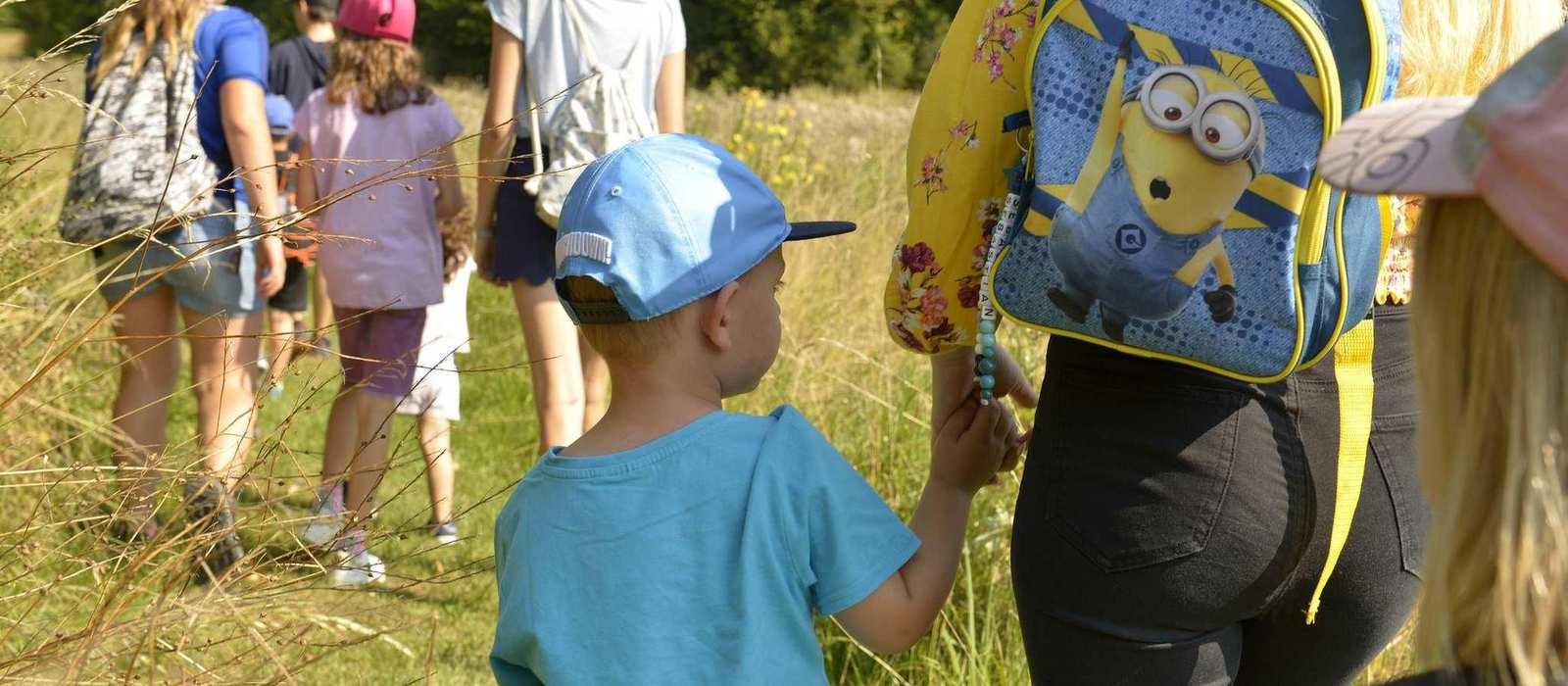 Ausflug von Kindern und Betreuungspersonal auf einer sonnigen Waldwiese. Im Hintergrund stehen Bäume.
