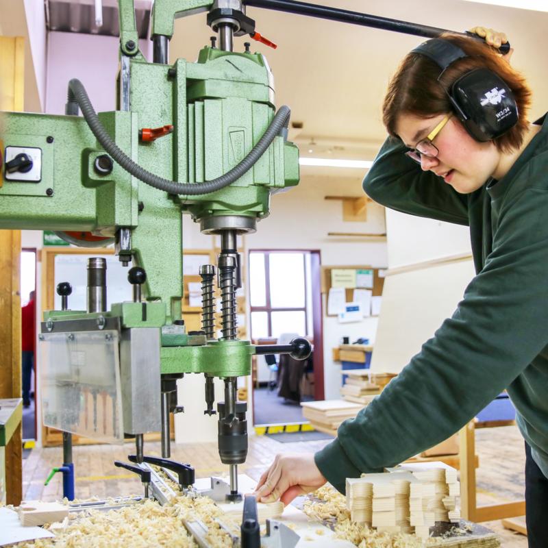 Eine Frau mit Ohrschützern betätigt eine große Bohrmaschine.