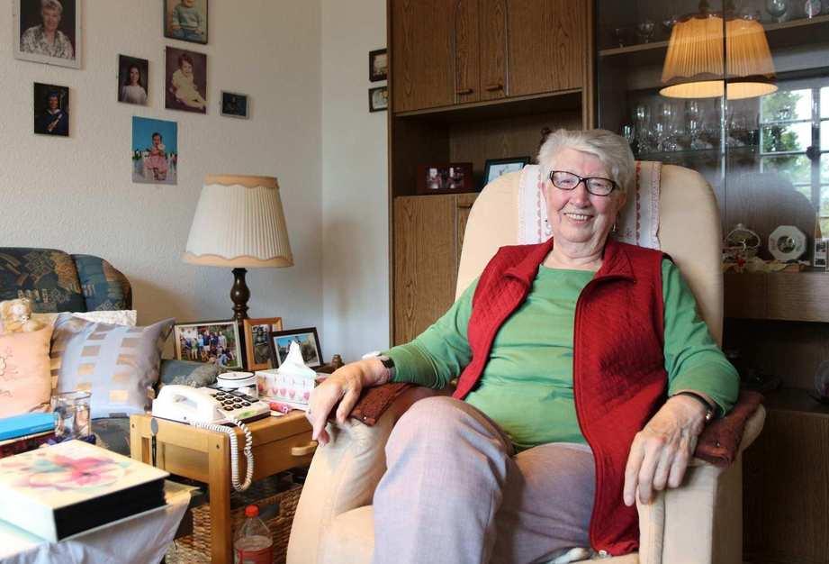 Eine ältere Frau mit Brille sitzt in ihrem Wohnzimmer in einem Sessel. Neben ihr steht ein Beistelltisch mit Telefon und Familienfotos.