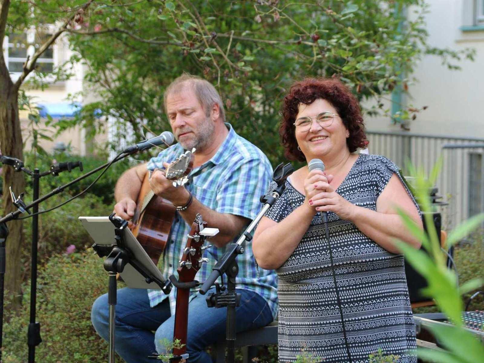 Ein Mann und eine Frau musizieren in einem Garten. Der Mann spielt Gitarre, die Frau singt mit einem Mikrophon.
