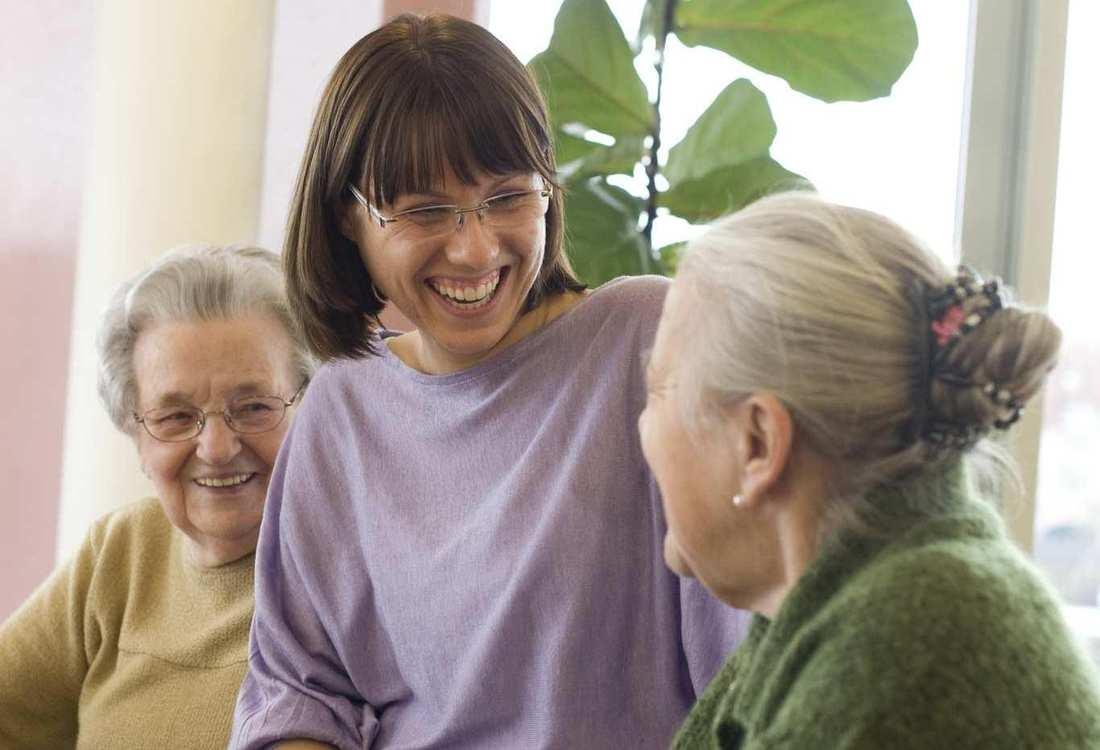 Drei Frauen unterhalten sich. Sie wirken alle sehr fröhlich. Im Hintergrund ist eine großblättrige Pflanze.