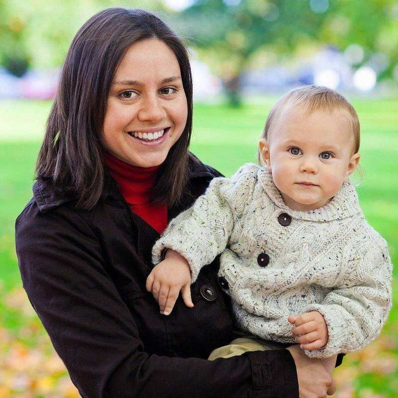 Eine junge Frau hält ein Kleinkind auf dem Arm. Im Hintergrund ist ein Park mit großer Wiese zu sehen.