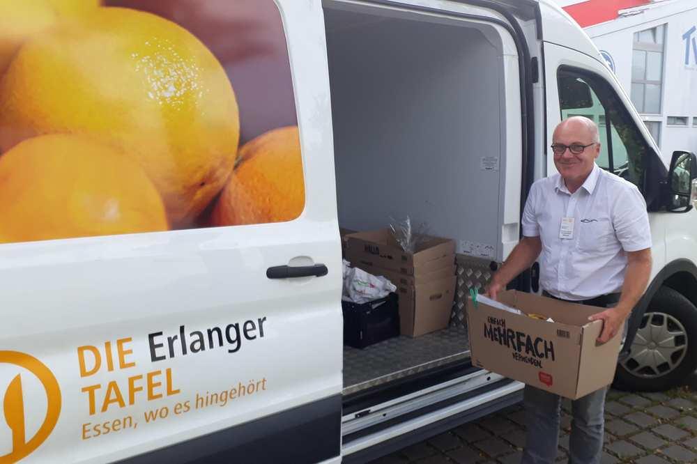 Ein Fahrer der Tafel lädt Kisten mit Lebensmitteln aus seinem Kleintransporter aus.
