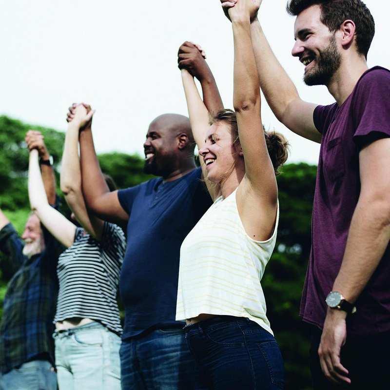 Acht Personen stehen in einer Reihe und halten sich an den erhobenen Händen. Sie lachen.