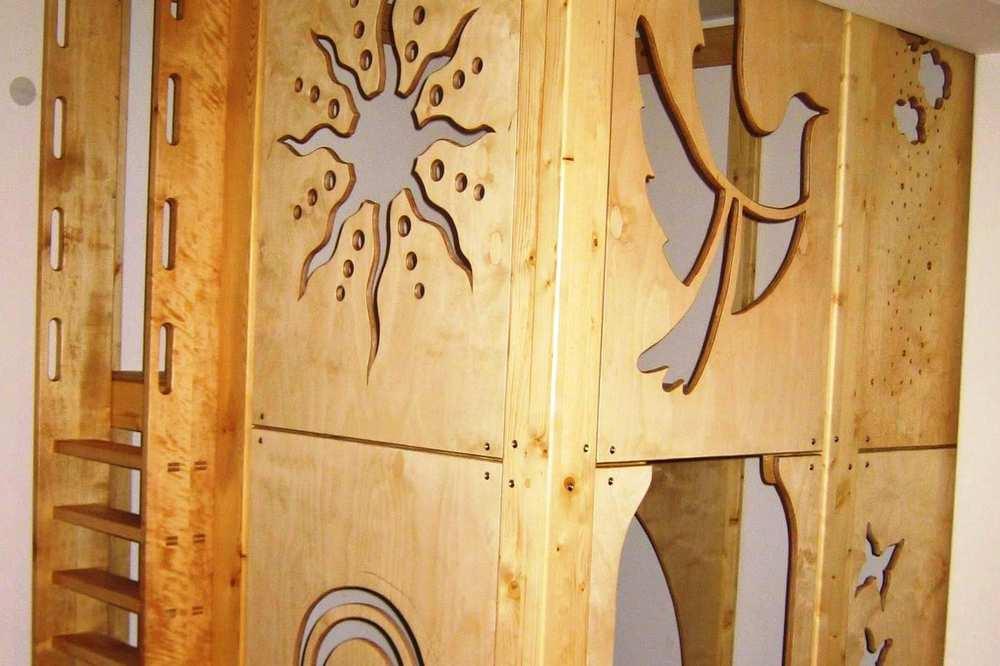 Eine Spielelandschaft auf zwei Ebenen. Auf die zweite Ebene gelangt man mit einer Leiter. Aus den Holzplatten sind verschiedene Figuren herausgeschnitzt, etwa eine Sonne oder ein Vogel.