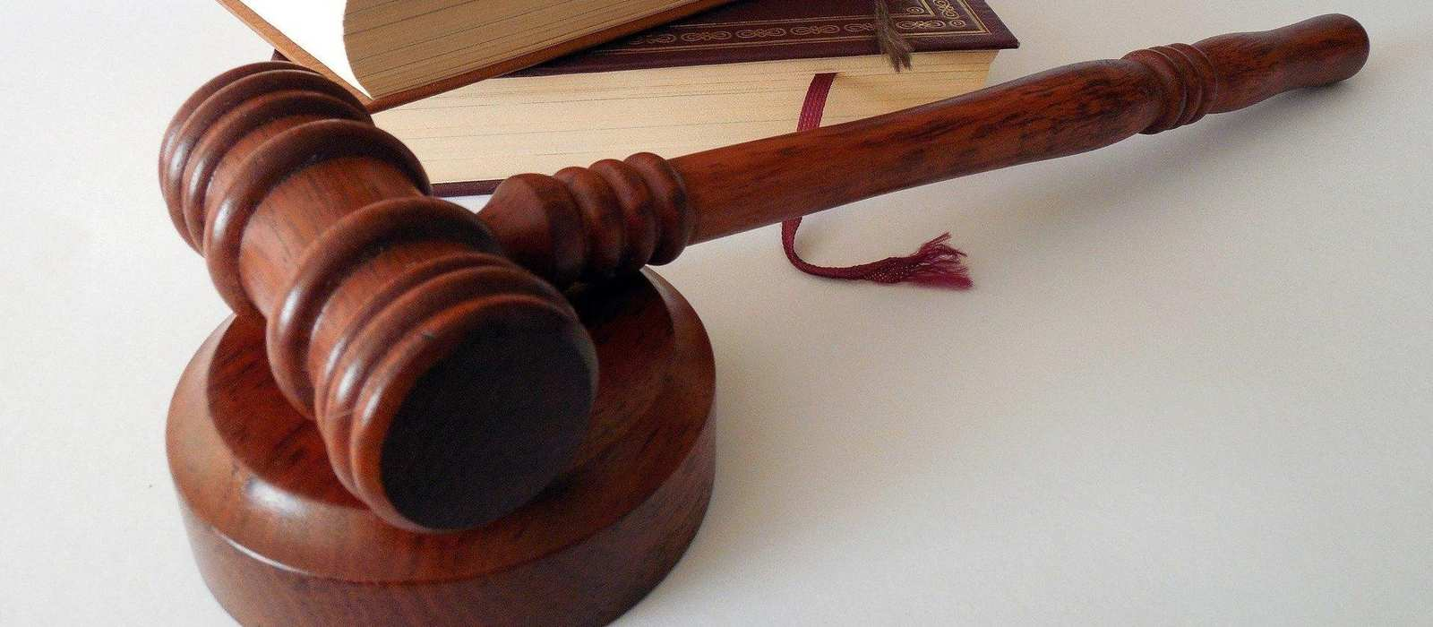 Ein Richterhammer und ein Gesetzbuch.