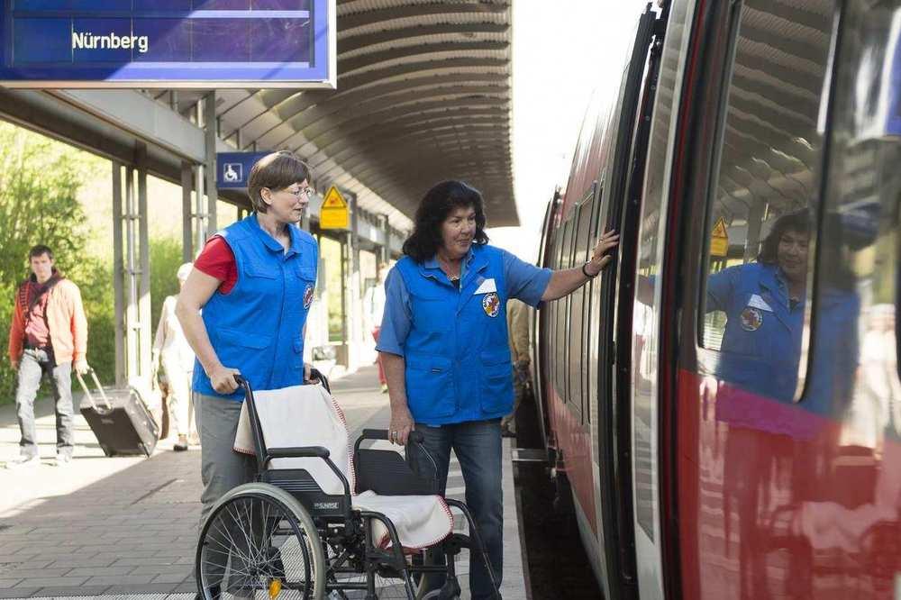 Zwei Mitarbeiterinnen der Bahnhofsmission stehen mit einem Rollstuhl vor einer geöffneten Zugtür.