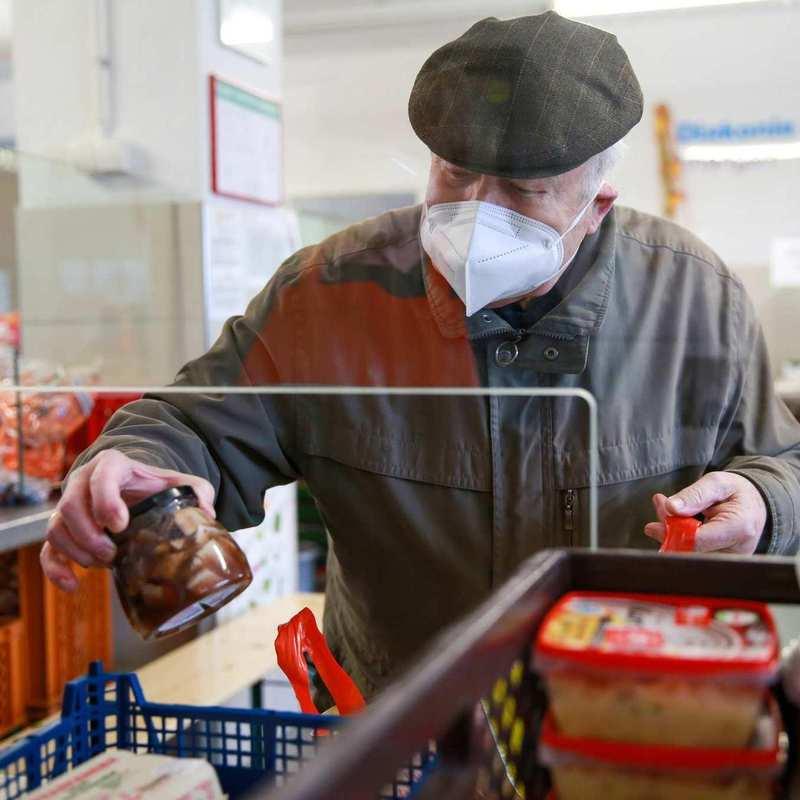 Eine älterer Herr packt ein Glas Eingemachtes in seine Tasche.