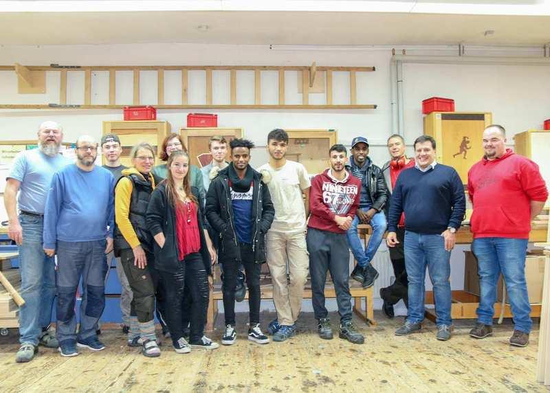 Vierzehn Personen stehen in einem Werkstattraum zu einem Gruppenbild zusammen.