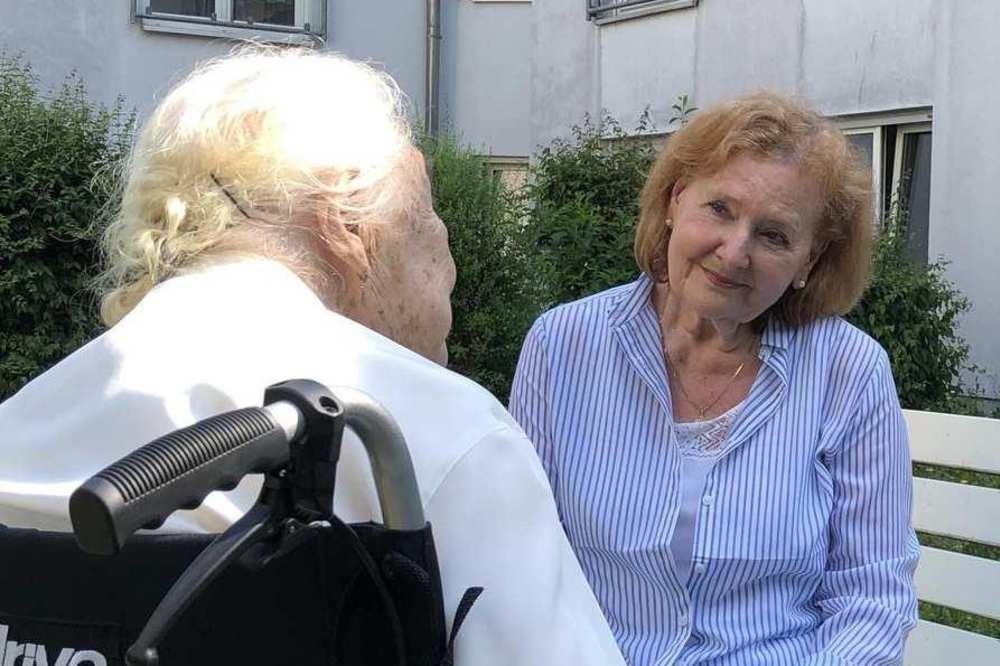 Drei Frauen sind im Außenbereich der Diakonie Sophienstraße ins Gespräch vertieft. Eine Frau sitzt in ihrem Rollstuhl, während eine andere ihr gegenübe rauf einer Bank sitzt. Die dritte Frau steht hinter der Bank.