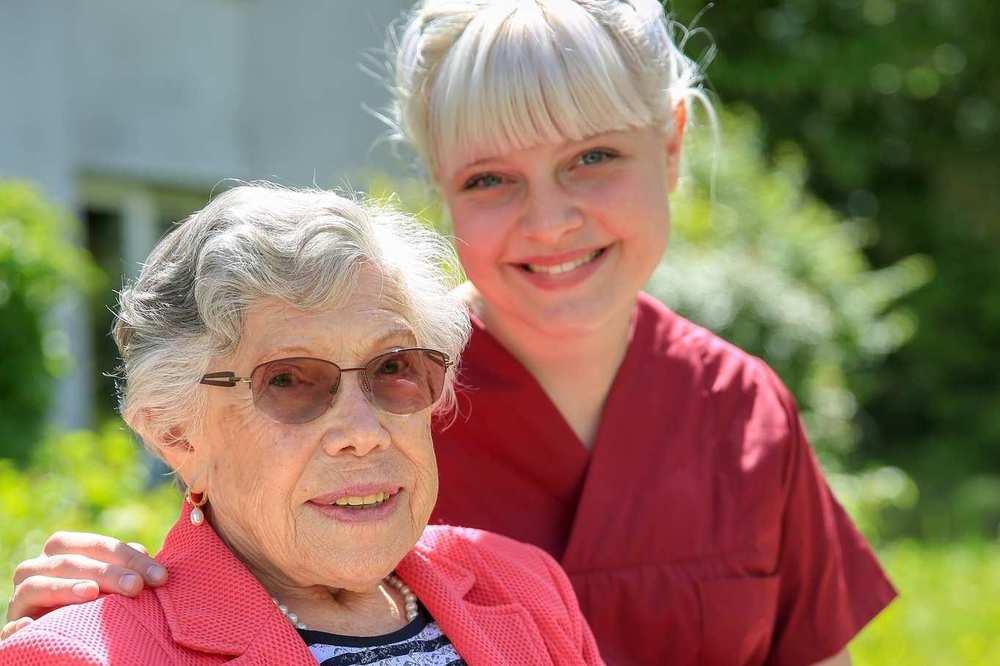 Eine ältere Bewohnerin mit Brille und eine Pflegekraft sitzen auf einer Bank im Garten.