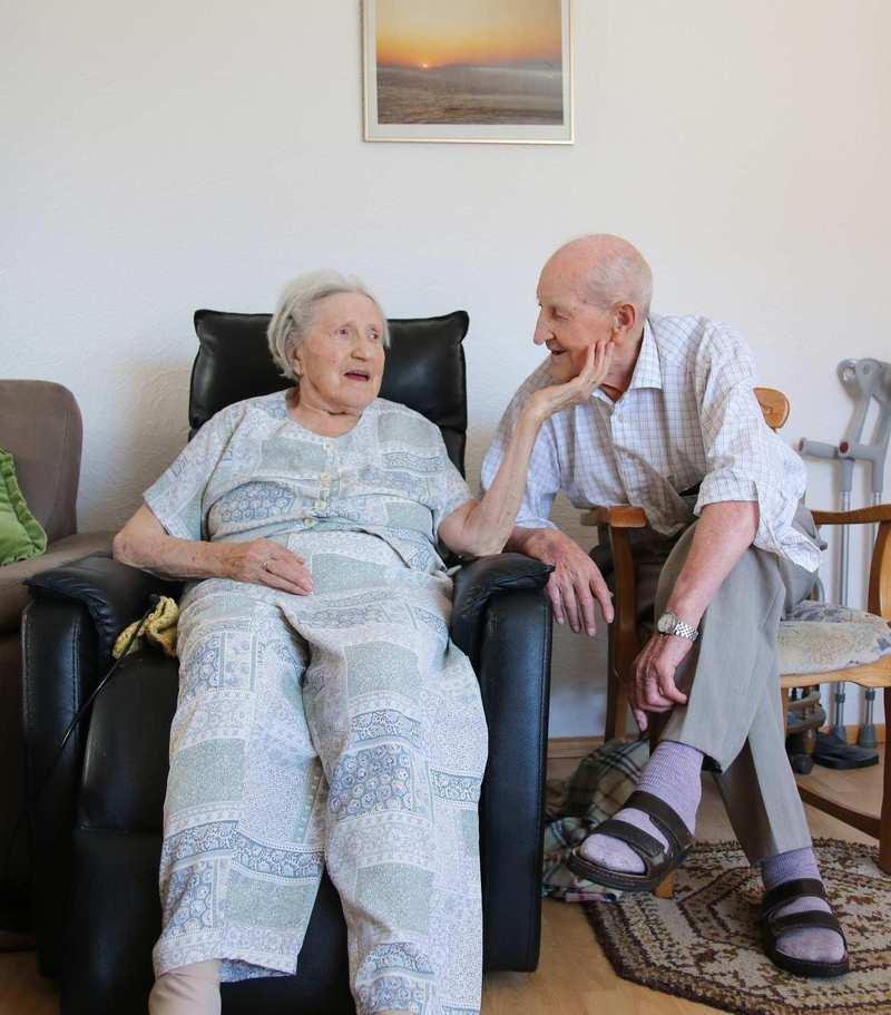 Ein älteres Ehepaar in ihrem Wohnzimmer. Die Frau sitzt in einem Sessel, der Mann neben ihr auf einem Stuhl.