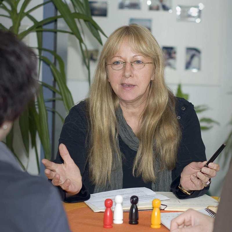 Drei Personen sitzen an einem Tisch. Eine Frau spricht zu einer Frau und einem Mann.