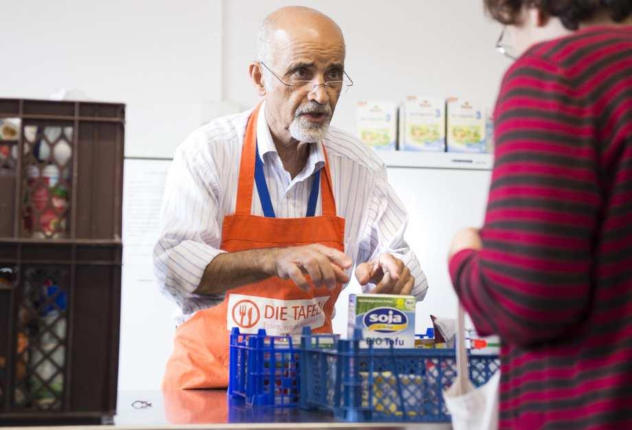 Ein Mitarbeiter der Tafel beugt sich über eine Kiste mit Lebensmittel.