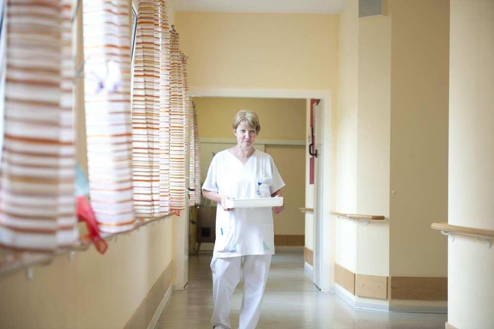 Eine Pflegekraft geht einen lichtdurchfluteten Gang entlang.