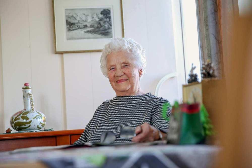 Eine ältere Frau sitzt an einem Tisch. Im Hintergrund hängt ein Bild an der Wand.