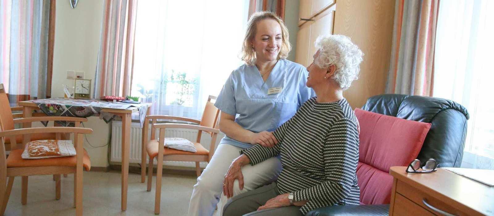Eine ältere Frau sitzt in einem Sessel und spricht mit der neben ihr stehenden Pflegekraft.