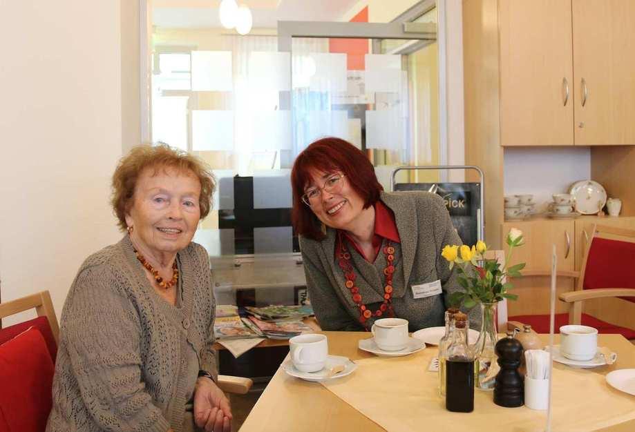 Zwei Frauen sitzen an einem Tisch und trinken Kaffee. Auf dem Tisch steht eine Vase mit Blumen.