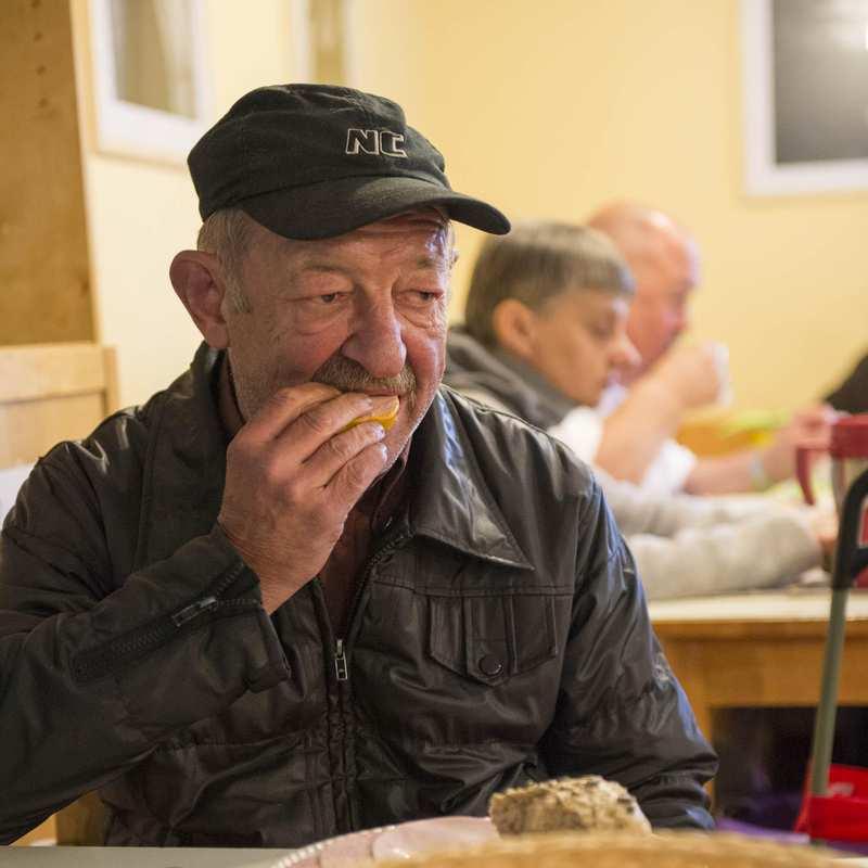 Ein älterer Mann mit abgetragener Jacke sitzt in einem Gemeinschaftsraum und isst ein Stück Brot. Im Hintergrund sind weitere Menschen an einem Tisch.