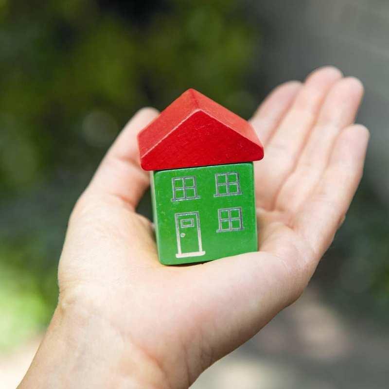 Eine Hand hält ein kleines Haus, das auch zwei Spielzeug-Klötzchen besteht.